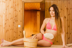 Woman in sauna with exfoliating glove. Skincare. Woman girl in spa sauna relaxing massaging skin with exfoliating glove. Skincare concept Royalty Free Stock Images