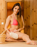 Woman in sauna with exfoliating glove. Skincare. Stock Photography