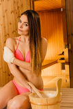 Woman in sauna with exfoliating glove. Skincare. Royalty Free Stock Photography