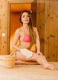 Woman in sauna with exfoliating glove. Skincare. Stock Photo
