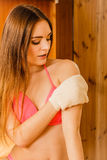 Woman in sauna with exfoliating glove. Skincare. Young woman in wood finnish spa sauna massaging skin with exfoliating glove. Girl in bikini relaxing. Skincare Stock Photography