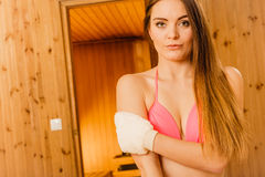 Woman in sauna with exfoliating glove. Skincare. Young woman in wood finnish spa sauna massaging skin with exfoliating glove. Girl in bikini relaxing. Skincare Stock Images