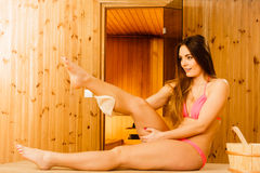 Woman in sauna with exfoliating glove. Skincare. Young woman in wood finnish spa sauna massaging skin with exfoliating glove. Girl in bikini relaxing. Skincare Royalty Free Stock Images