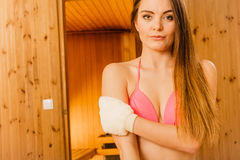 Woman in sauna with exfoliating glove. Skincare. Young woman in wood finnish spa sauna massaging skin with exfoliating glove. Girl in bikini relaxing. Skincare Royalty Free Stock Photos