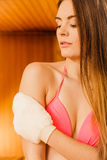 Woman in sauna with exfoliating glove. Skincare. Young woman in wood finnish spa sauna massaging skin with exfoliating glove. Girl in bikini relaxing. Skincare Stock Image