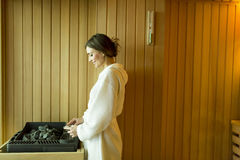 Woman in the sauna. Woman pouring water over the rocks in the sauna stock photos
