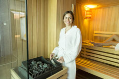 Woman in the sauna. Woman pouring water on the rocks in the sauna royalty free stock image