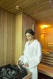 Woman in the sauna. Woman pouring water on the rocks in the sauna royalty free stock photos