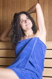 Woman in a sauna with towel relaxing Stock Photo