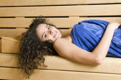 Woman in a sauna with towel relaxing Royalty Free Stock Photography