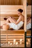 Woman in sauna. Young woman in white towel pouring water while resting in Finnish sauna royalty free stock photography