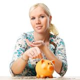 Woman saving her money in piggy bank. Portrait of a woman saving her money in piggy bank. Isolated over white background royalty free stock photo