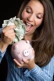 Woman Saving Money. In piggybank Royalty Free Stock Images