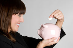 Woman Saving Money. In piggybank stock photography
