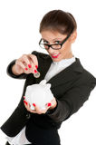 Woman saving money. Woman in glasses saving money in a piggybank - isolated over a white background Royalty Free Stock Image
