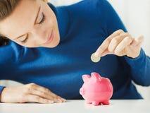 Woman saving money in piggy bank stock image