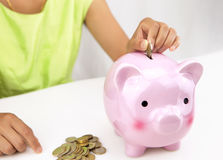 Woman saving money in piggy bank Royalty Free Stock Photos