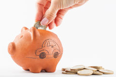 Woman saving money into a traditional clay piggy b stock image