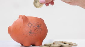 Woman saving money into a traditional clay piggy bank for holidays stock video footage