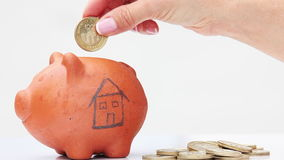 Woman saving money into a traditional clay piggy bank for a house. Close up of a woman saving money into a traditional clay piggy bank for a house stock video