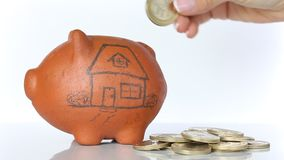Woman saving money into a traditional clay piggy bank for a house stock video footage