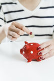 Woman Saving Money With Red Piggy Bank Royalty Free Stock Images