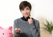 Woman savings coin in the piggy bank. Young woman smiling and thinking about savings, coins in the hand and pink piggy bank on desktop Stock Photo