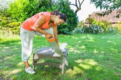 Woman sawing wood outside with handsaw Royalty Free Stock Image