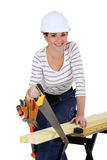Woman sawing wood Stock Images