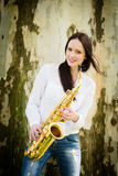 Woman with saxophone in nature Stock Image