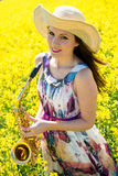Woman with saxophone in rapeseed field Stock Image