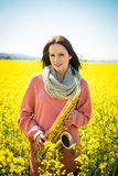 Woman with saxophone in rapeseed field Royalty Free Stock Image