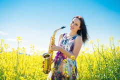Woman with saxophone in rapeseed field Royalty Free Stock Photos