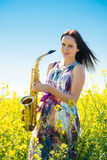 Woman with saxophone in rapeseed field Royalty Free Stock Images