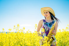 Woman with saxophone in rapeseed field Stock Images