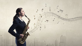 Woman saxophonist. Concept image. Young woman playing saxophone and notes coming out Royalty Free Stock Photo