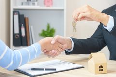 Woman say yes to sign loan contract for buying new home concept. With key - hand shaking royalty free stock image
