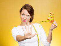 Woman saying no to fatty pizza with measuring tape around, trying to resist temptation to eat it Royalty Free Stock Image