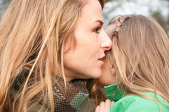 Woman saying something to her daugther's ear Stock Photography