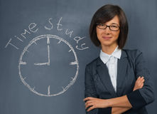 Woman says time study. Young woman in a suit is standing near the blackboard, on which is written time study Stock Image