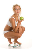 Young woman with apple on bathroom scale Stock Photos