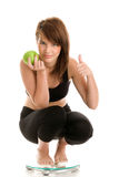 Woman on scale. Young woman on scale with green apple isolated on white background Stock Images