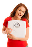 Woman with scale happy with her weight isolated over white backg Stock Photo