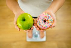 Woman on scale measuring weight holding apple and donuts choosing between healthy or unhealthy food. Close up of woman on scale holding on hands apple and royalty free stock image