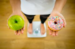 Woman on scale measuring weight holding apple and donuts choosing between healthy or unhealthy food royalty free stock photo