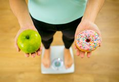 Woman on scale measuring weight holding apple and donuts choosing between healthy or unhealthy food royalty free stock photos