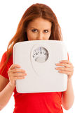 Woman with scale unhappy with her weight gesturing sadness and w Stock Image