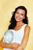Woman with scales after a successful diet. A young woman with a balance in his hand smiling after a successful diet Stock Image