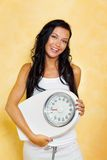 Woman with scales after a successful diet. A young woman with a balance in his hand smiling after a successful diet Royalty Free Stock Photo