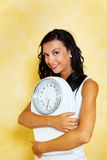 Woman with scales after a successful diet. A young woman with a balance in his hand smiling after a successful diet Stock Photos